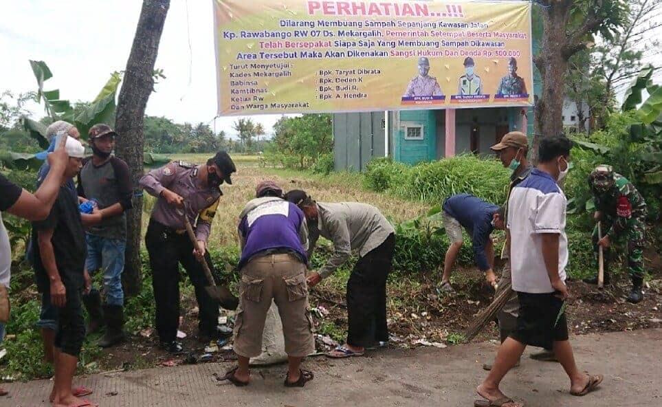 aparat kepolisian dan TNI gotong royong membersihkan sampah dipinggir jalan yang dibuang sembarangan oleh warga